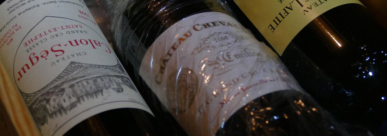 Weinankauf aus einem Privatbesitz. Zu sehen sind 3 Weinflaschen, lange Jahre gelagert in einem Weinkeller